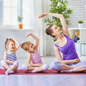 mom and 2 girls doing yoga to relax since we have the solution for head lice